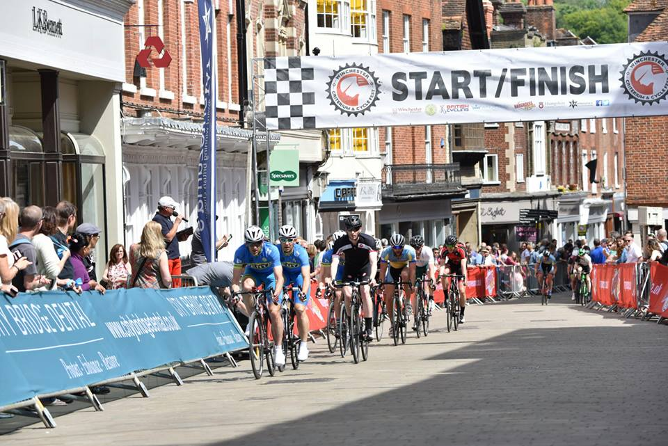 Cyclists cross the finish line at Winchester Criterium 2016 - the branded banners show an example of local event sponsorship